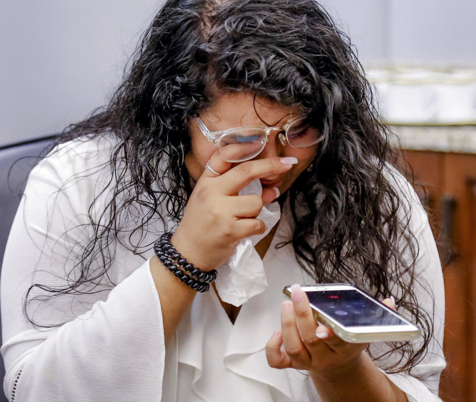 Photo - Destiny Pinon, dries her tears while she talks to her mother, Juanita Peralta. Pinon was joined by two sisters and a brother in being the first to call their mother and tell her she would be coming home after her sentence was commuted. After placing her signatures on the required documents during a ceremony in the Governor's conference room, Gov. Mary Fallin officially commuted the sentences of 21 Oklahoma inmates who were serving sentences 10 years or longer for drug possession and other crimes that now carry lesser punishments following recent reforms approved by voters and state lawmakers. The inmates were assisted through a commutation campaign led by Oklahomans for Criminal Justice Reform. During the emotional event at the Capitol on  Wednesday, Dec. 5, 2018, Fallin signed the commutations one by one for the first group of applicants to make it to her desk after a two-stage review by the Oklahoma Pardon and Parole Board.