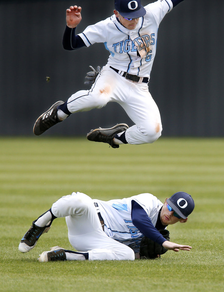 Photo - Oktaha second baseman Harley Shaffer leaps over teammate and right fielder Tyler Goad after Goad made a diving catch of  a Dale hit he and Shaffer were both running to catch in shallow right field during the Class 2A baseball state semifinal game at Shawnee High School on Friday, May 10, 2019. Oktaha was defeated by Dale, 6-0.    [Jim Beckel/The Oklahoman]