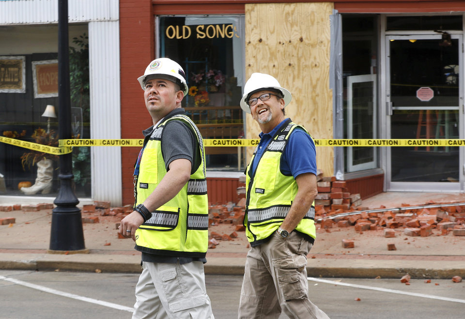 Photo - Two men look at damage to the top of a building on E. Broadway  in downtown Cushing. They operate a drone service out of Tulsa and were brought in to assist with initial damage assessment to structures in the Cushing downtown district. Damage in  Cushing on Monday, Nov. 7, 2016, caused by Sunday night's 5.0 magnitude earthquake. Photo by Jim Beckel, The Oklahoman