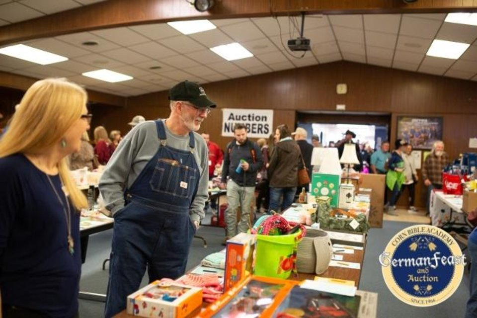 Photo -  People view auction items at Corn Bible Academy's 2019 German Feast and Auction in Corn. [Photo provided]