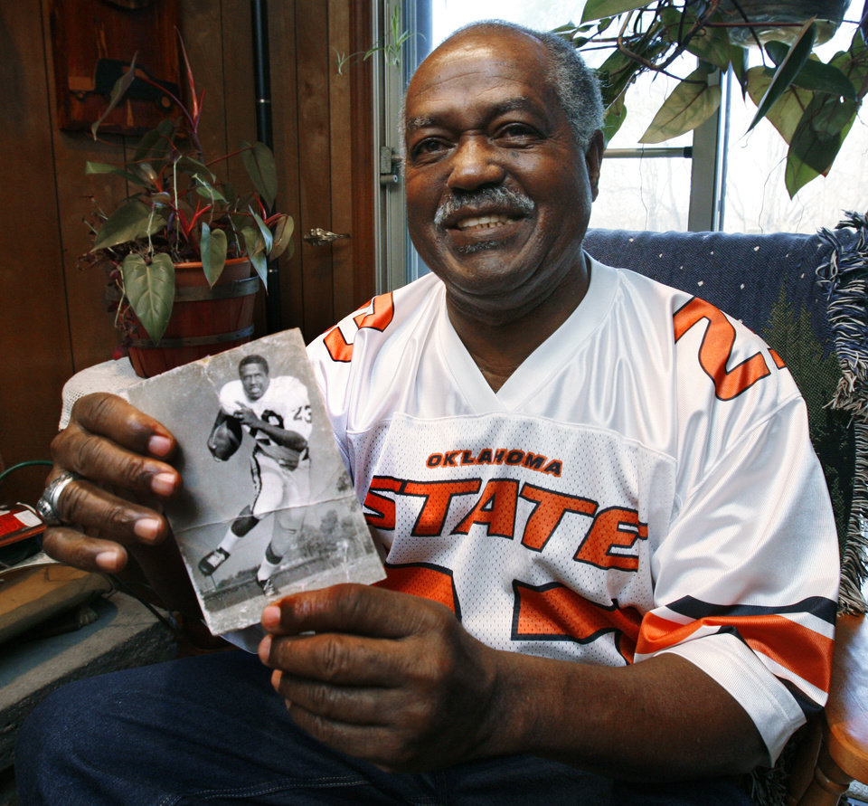 Photo - FORMER OKLAHOMA STATE UNIVERSITY (OSU) COLLEGE FOOTBALL PLAYER: Chester Pittman is shown at his home on Friday, November 6, 2009, in Kansas City, Kansas.  He became the first black man to earn a football letter exactly 50 years ago this season.  The photograph in his hands is a college publicity photograph from his days at Oklahoma State University. Photo by Steve Sisney, The Oklahoman ORG XMIT: KOD