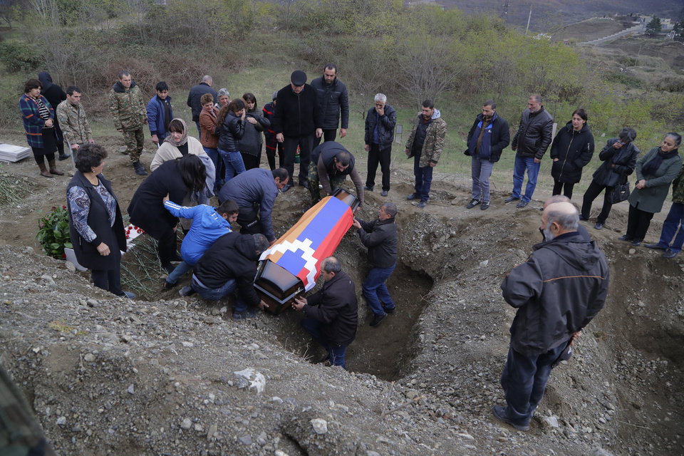 Photo -  Relatives and friends of Mkhitar Beglarian, an ethnic Armenian soldier of Nagorno-Karabakh army who was killed during a military conflict, lower the coffin into aa grave during a funeral at a cemetery in Stepanakert, the separatist region of Nagorno-Karabakh, on Sunday, Nov. 15, 2020. Ethnic Armenian forces had controlled Nagorno-Karabakh and sizeable adjacent territories since the 1994 end of a separatist war. Fighting resumed in late September and have now ended with an agreement that calls for Azerbaijan to regain control of the outlying territories as well as allowing it to hold on to parts of Nagorno-Karabakh that it seized during the fighting. (AP Photo/Sergei Grits)