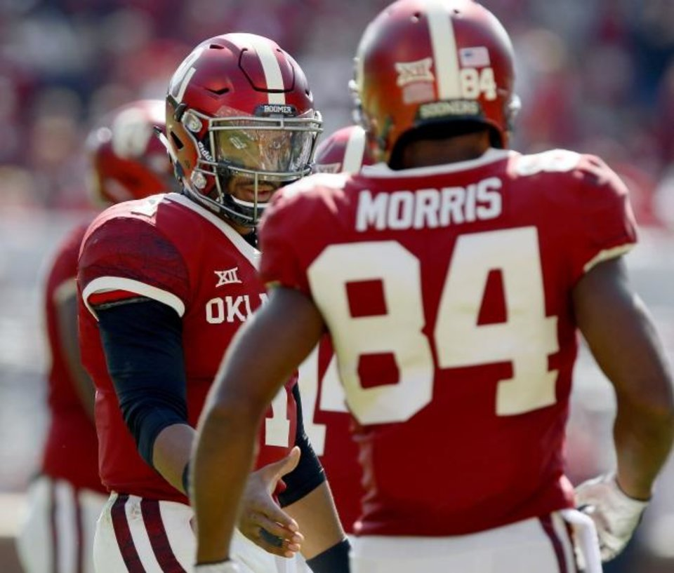 Photo -  Oklahoma's Jalen Hurts, left, reaches out to shake hands with Lee Morris after the pair connected for a touchdown pass during the Sooners' 52-14 win over West Virginia on Saturday in Norman. [Bryan Terry/The Oklahoman]