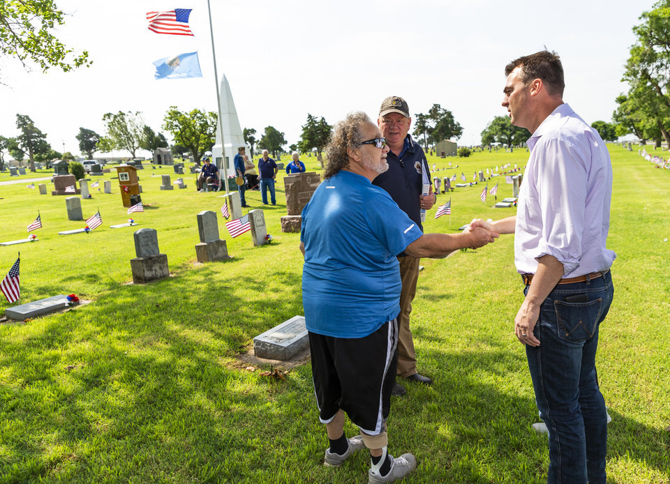 Photo - Gov. Kevin Stitt, right, shakes hands with Terry Walker at the El Reno Cemetery before the start of a Memorial Day service  in El Reno, Okla. on Monday, May 27, 2019. Gov. Stitt was in El Reno with mayor Matt White to tour the aftermath of a tornadoThe EF3 tornado hit the area on Saturday night killing two people and injuring many others. [Chris Landsberger/The Oklahoman]
