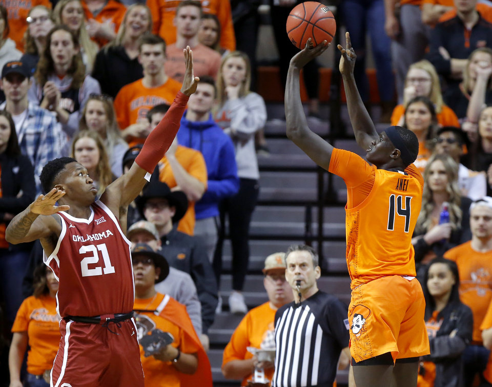 Photo - Oklahoma State's Yor Anei (14) shoots a basket over Oklahoma's Kristian Doolittle (21) during an NCAA men's Bedlam basketball game between the Oklahoma State University Cowboys (OSU) and the University of Oklahoma Sooners (OU) at Gallagher-Iba Arena in Stillwater, Okla., Saturday, Feb. 22, 2020. Oklahoma State won 83-66. [Bryan Terry/The Oklahoman]