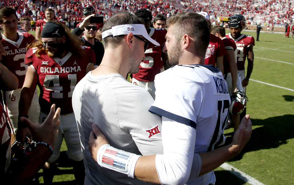 Photo - Oklahoma coach Lincoln Riley talks with West Virginia's Austin Kendall (12) after a college football game between the University of Oklahoma Sooners (OU) and the West Virginia Mountaineers at Gaylord Family-Oklahoma Memorial Stadium in Norman, Okla, Saturday, Oct. 19, 2019. Oklahoma won 52-14. [Bryan Terry/The Oklahoman]
