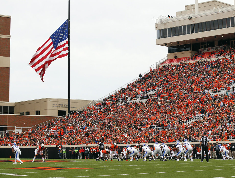 Photo - The American flag flies at half staff during a college football game between the Oklahoma State University Cowboys (OSU) and the Kansas Jayhawks (KU) at Boone Pickens Stadium in Stillwater, Okla., Saturday, Oct. 24, 2015. Photo by Nate Billings, The Oklahoman