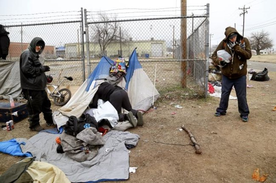 Photo -  People remove their possessions and disassemble tents as they prepare to leave a homeless encampment in Oklahoma City. [Oklahoman archives]