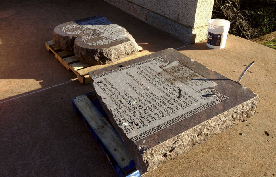 Photo - FILE - In this Oct. 24, 2014, file photo, the damaged remains of a Ten Commandments monument lie on the state Capitol grounds in Oklahoma City after driver, Michael Tate Reed of Van Buren, Ark., crashed into the statue. Tate was admitted to a hospital for mental treatment. Formal charges were never filed. On Wednesday, June 28, 2017, Reed was booked into jail in Little Rock on preliminary charges in connection with driving a vehicle into the newly installed Ten Commandments monument on the grounds of the state Capitol in Little Rock. (AP Photo/Sean Murphy, File)