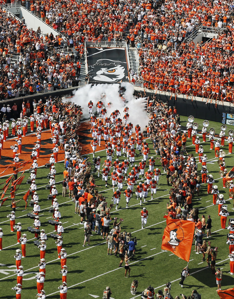 Photo - The OSU Cowboys take the field before a college football game between the Oklahoma State University Cowboys (OSU) and the TCU Horned Frogs at Boone Pickens Stadium in Stillwater, Okla., Saturday, Sept. 23, 2017. Photo by Nate Billings, The Oklahoman