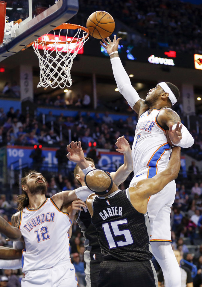 Photo - Oklahoma City's Carmelo Anthony (7) shoots over Sacramento's Vince Carter (15) next to Oklahoma City's Steven Adams (12) during an NBA basketball game between the Oklahoma City Thunder and the Sacramento Kings at Chesapeake Energy Arena in Oklahoma City, Monday, March 12, 2018. Photo by Nate Billings, The Oklahoman