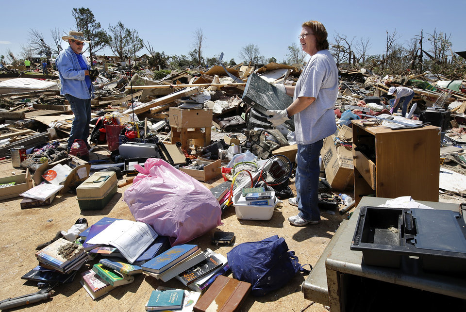 Photo - Relatives of John and Barbara DeCouser salvage items from their home in Steelman Estates in Bethel Acres on Wednesday, May 22, 2013. Their home was destroyed in Sunday evening's deadly tornado that swept through their small neighborhood leaving massive destruction.The DeCousers were in their home when the tornado ripped it apart. Both were taken to a hospital. John received head injuries and a fractured neck. He has been released. Barbara remains hospitalized with a back injury. Relatives said parts of two other homes landed on top of the DeCouser's home.   Photo  by Jim Beckel, The Oklahoman.