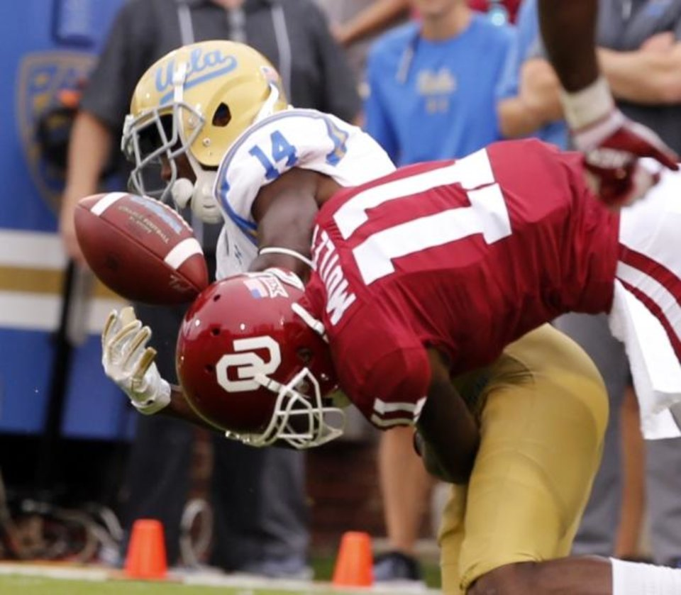 Photo -  Oklahoma's Parnell Motley (11) breaks up a pass to UCLA's Theo Howard during a game last season on Owen Field. The Sooners visit UCLA on Saturday inside the Rose Bowl. [OKLAHOMAN ARCHIVES]