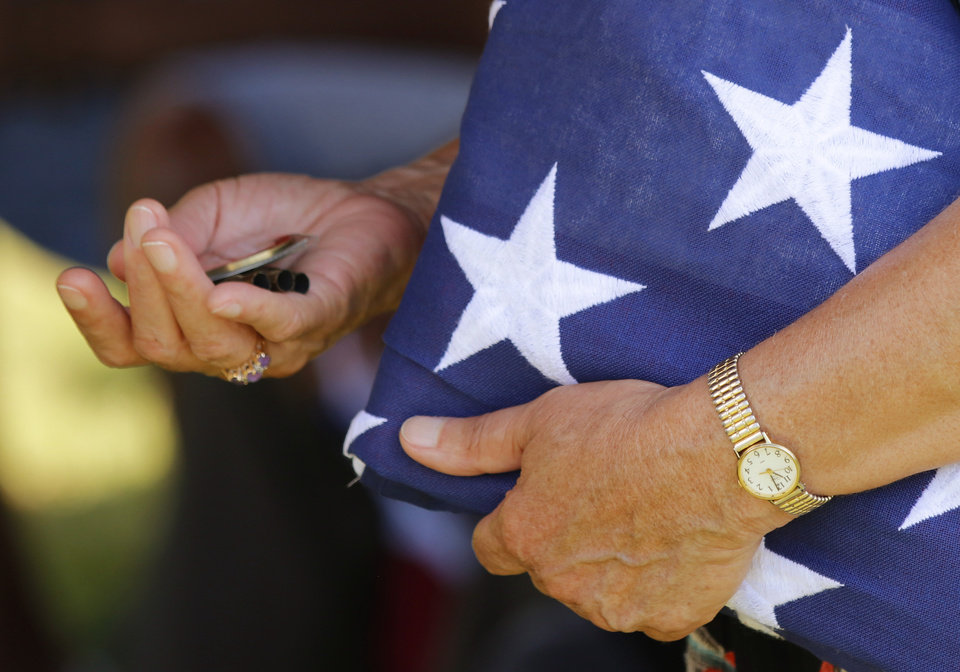 Photo - Alma Lucas, granddaughter of Ulysses Grant Moore holds the American flag and shell casings from the 21 gun salute presented to her at the memorial for U.G. Moore, a WWI vet whose grave marker never make it to his grave at Trice Hill Cemetery, until 55 years after his death, Tuesday, July 16, 2019. [Doug Hoke/The Oklahoman]