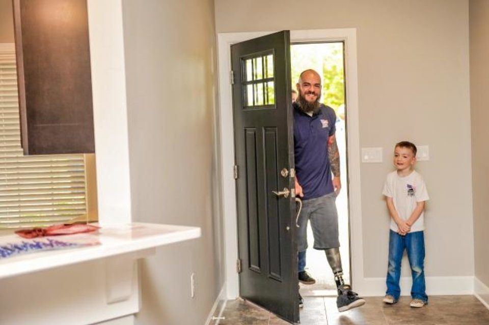 Photo -  U.S. Army Spc. Adam Putt and son Victor walked into their new Blanchard home, donated by Homes For Our Troops. [HFOT]