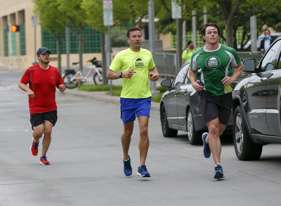 Photo - Runners travel south on Harvey Ave. outside the Oklahoma City National Memorial and Museum on the 25th anniversary of the bombing of the Alfred P. Murrah Federal Building, in Oklahoma City, Sunday, April 19, 2020. The memorial remains closed and did not hold a live remembrance ceremony because of the coronavirus pandemic. [Nate Billings/The Oklahoman]