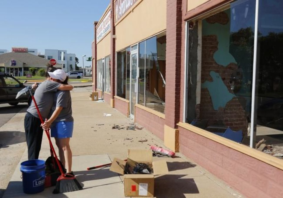 Photo -  Deette Hankins, left, hugs Angie Mendez, owner of The Saucee Sicilian, as she arrives to help clean broken glass on Sunday from the location they are building on Classen Blvd. Damage occurred Saturday night during protests in downtown Oklahoma City. [Doug Hoke/The Oklahoman]