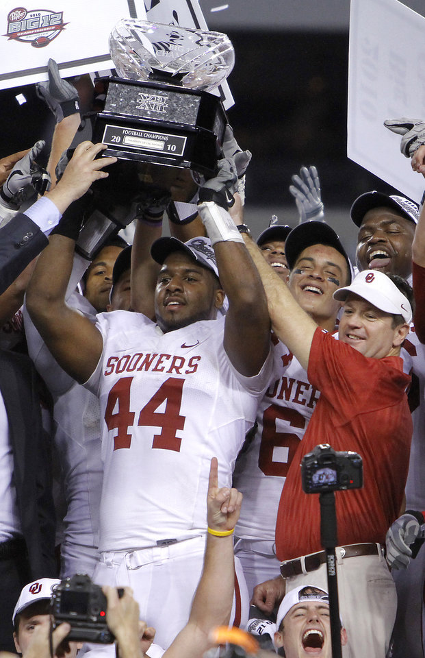 Photo - Oklahoma's Jeremy Beal and coach Bob Stoops hold up the Big 12 Championship trophy after the 23-20 win over Nebraska during the Big 12 football championship game between the University of Oklahoma Sooners (OU) and the University of Nebraska Cornhuskers (NU) at Cowboys Stadium on Saturday, Dec. 4, 2010, in Arlington, Texas.  Photo by Chris Landsberger, The Oklahoman