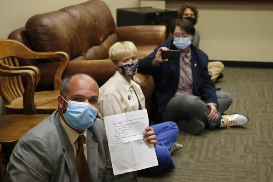 Photo -  Jess Eddy, left, holds a list of demands as a group of protestors sit-in at the office of Oklahoma County District Attorney David Prater on Monday in Oklahoma City. [AP Photo/Sue Ogrocki]