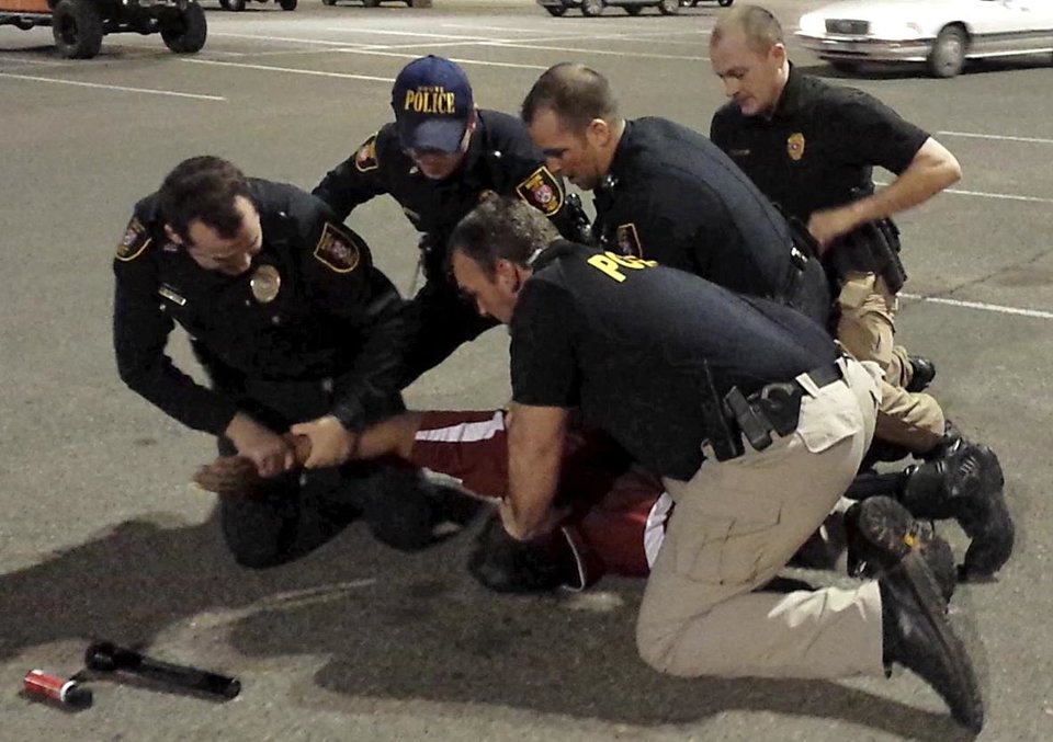 Photo -  Left: This cellphone video screen capture shows Moore police officers restraining Luis Rodriguez in the parking lot at the Warren Theatre on Feb. 15. Rodriguez died after the incident and the state medical examiner's office Wednesday announced that Rodriguez's death is classified as a homicide.  PHOTO PROVIDED