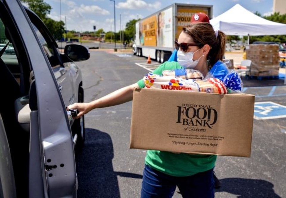 Photo -  Katelyn Gleason-Dockery loads a box of food into a client's car Wednesday during a Regional Food Bank of Oklahoma food distribution event for individuals seeking unemployment assistance in Midwest City.  [Chris Landsberger/The Oklahoman]