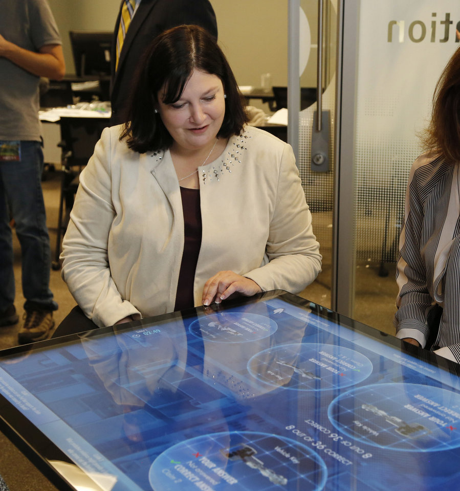 Photo -  Oklahoma City Superintendent Aurora Lora works an educational touch screen Monday at the Oklahoma City National Memorial & Museum. [Photo by Paul Hellstern, The Oklahoman]