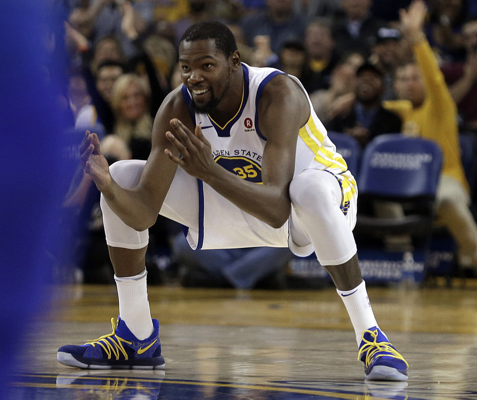 Photo - Golden State Warriors' Kevin Durant celebrates after scoring against the Orlando Magic during the second half of an NBA basketball game Monday, Nov. 13, 2017, in Oakland, Calif. The Warriors won 110-100. (AP Photo/Ben Margot)