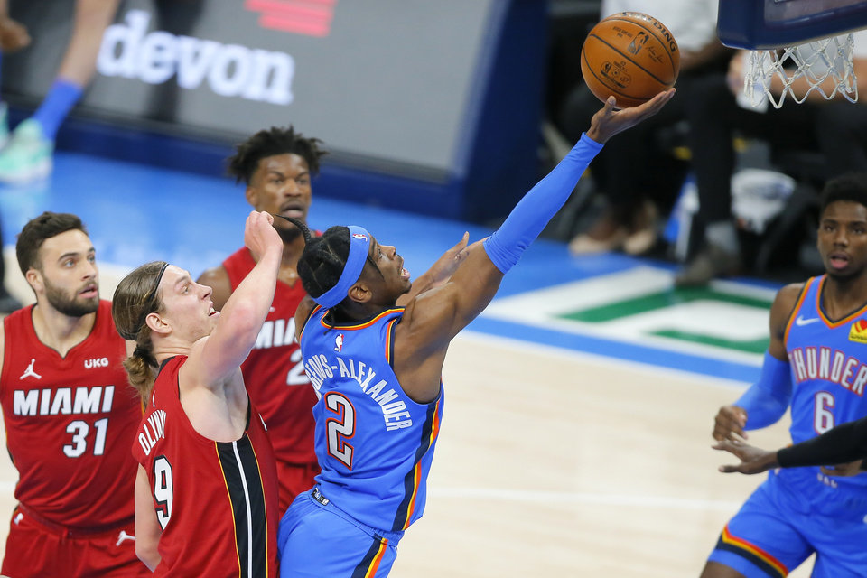 Photo - Oklahoma City's Shai Gilgeous-Alexander (2) goes past Miami's Kelly Olynyk (9) during an NBA basketball game between the Oklahoma City Thunder and the Miami Heat at Chesapeake Energy Arena in Oklahoma City, Monday, Feb. 22, 2021. [Bryan Terry/The Oklahoman]