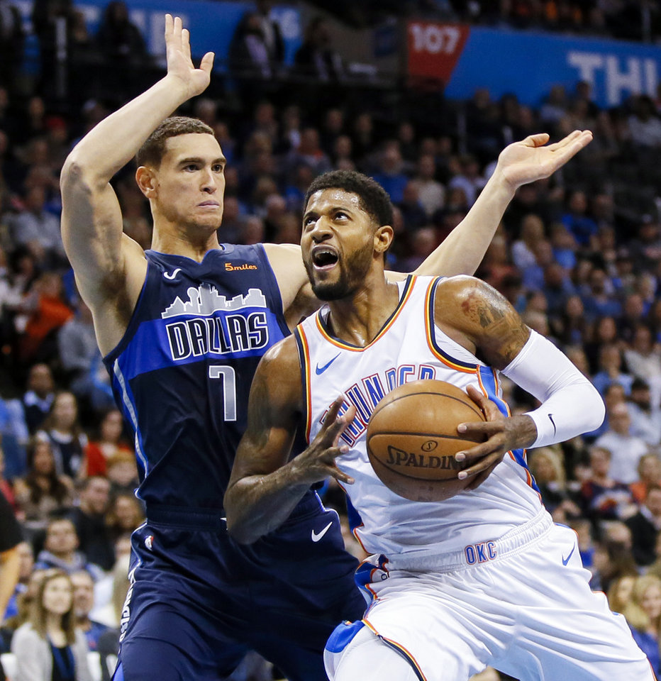 Photo - Oklahoma City's Paul George (13) drives against Dallas' Dwight Powell (7) during an NBA basketball game between the Oklahoma City Thunder and Dallas Mavericks at Chesapeake Energy Arena in Oklahoma City, Monday, Dec. 31, 2018. Photo by Nate Billings, The Oklahoman
