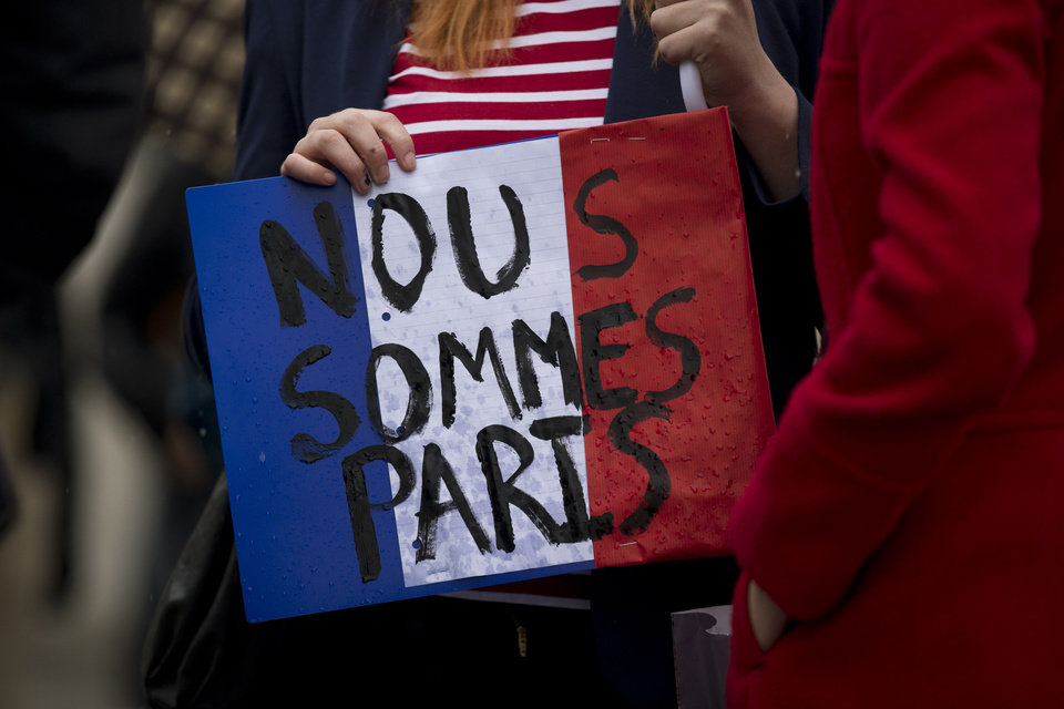 "Photo - A woman holds a French flag colored placard with French translating as ""we are Paris"" whilst attending a vigil for victims of the deadly Paris attacks, in Trafalgar Square, London, Saturday, Nov. 14, 2015. French President Francois Hollande said more than 120 people died Friday night in shootings at Paris cafes, suicide bombings near France's national stadium and a hostage-taking slaughter inside a concert hall. (AP Photo/Matt Dunham)"