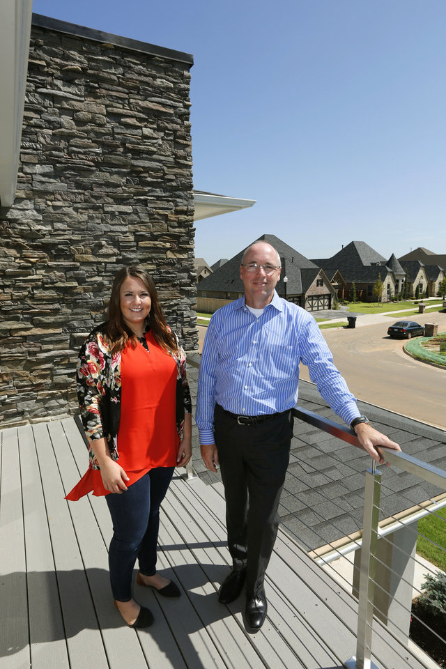 Photo -  Kayla Watson, lead designer for TimberCraft Homes, and Jack Evans, company founder, stand on the balcony of the St. Jude Dream Home at 15201 Kestral Way in the Lakes at Traditions addition, northwest of NW 150 and Santa Fe Avenue.