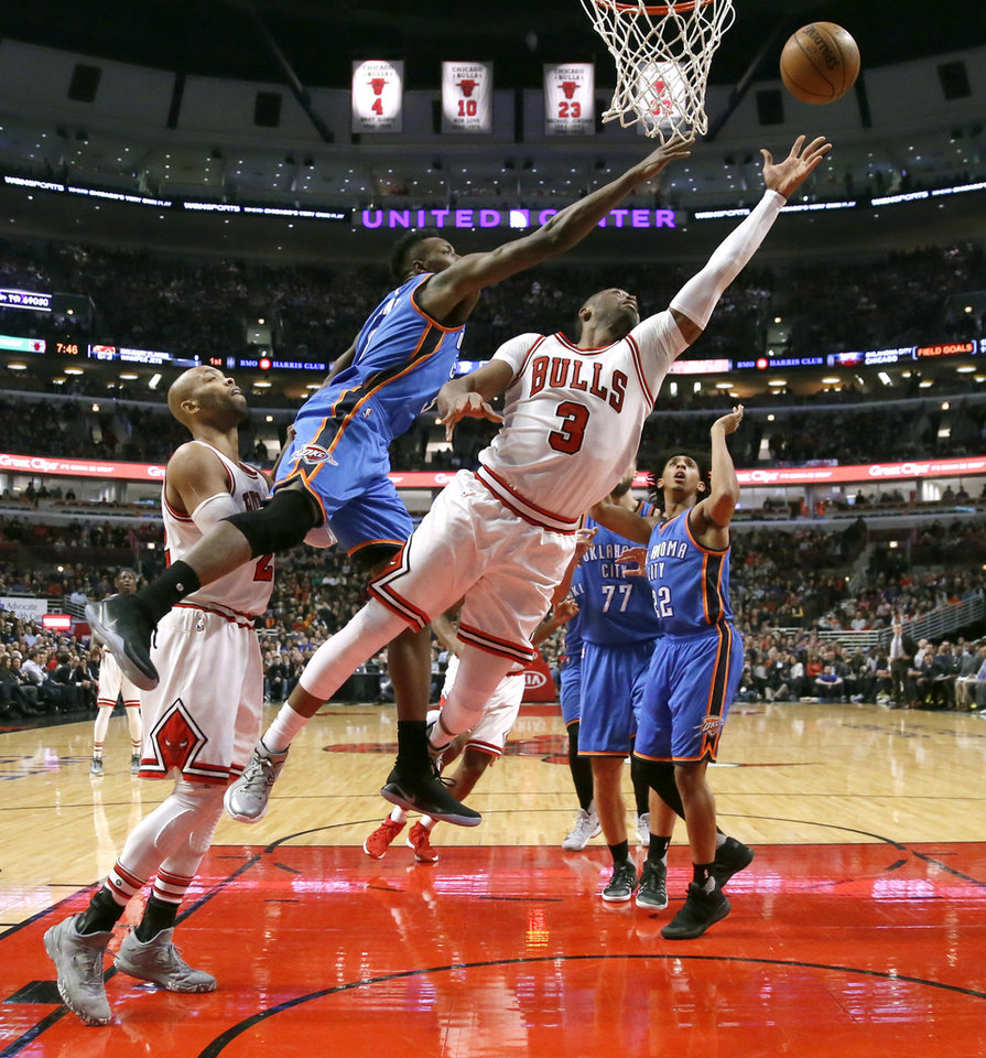 Photo - Chicago Bulls' Dwyane Wade (3) shoots  layup past Oklahoma City Thunder's Jerami Grant, center, as Cameron Payne watches during the first half of an NBA basketball game Monday, Jan. 9, 2017, in Chicago. (AP Photo/Charles Rex Arbogast)