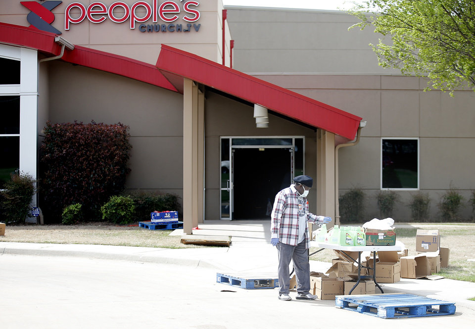 Photo - Larry J. McNeal loads supplies and groceries into cars at PeopleÕs Church, 800 E. Britton Rd., in Oklahoma City, Thursday, April 9, 2020. Cars lined up for miles for hours as the church members gave away 6,000 pounds of free groceries and supplies. [Sarah Phipps/The Oklahoman]