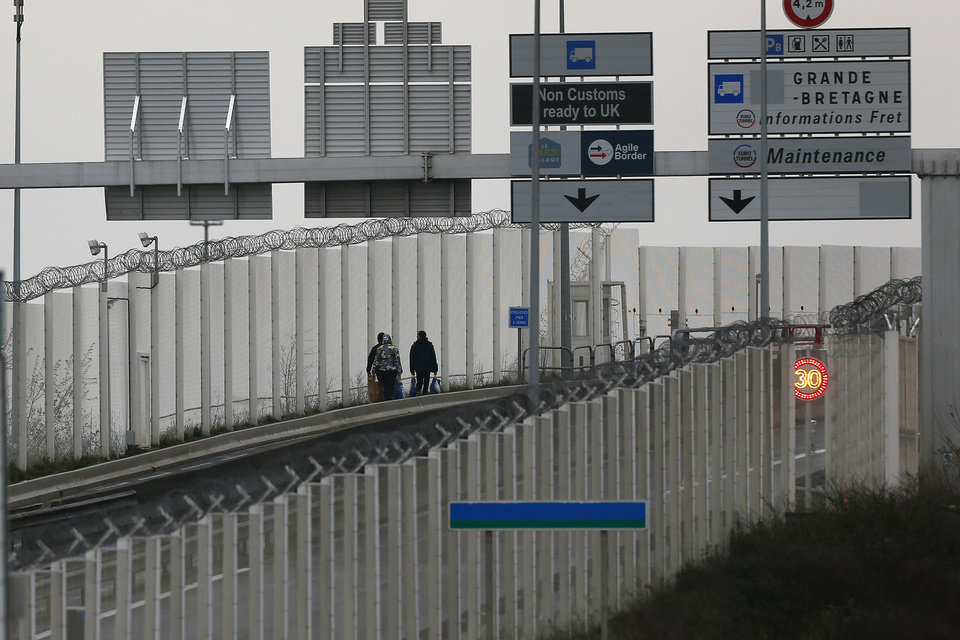 Photo -  Migrants walk toward the check point on the Eurotunnel site in Coquelles, Monday Jan.4, 2021. Britain left the European bloc's vast single market for people, goods and services, completing the biggest single economic change the country has experienced since World War II. (AP Photo/Michel Spingler)