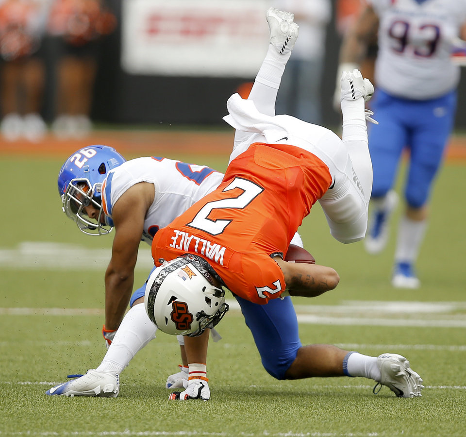 Photo - Oklahoma State's Tylan Wallace (2) flies over Boise State's Avery Williams (26) during a college football game between the Oklahoma State University Cowboys (OSU) and the Boise State Broncos at Boone Pickens Stadium in Stillwater, Okla., Saturday, Sept. 15, 2018. Oklahoma State won 44-21. Photo by Bryan Terry, The Oklahoman
