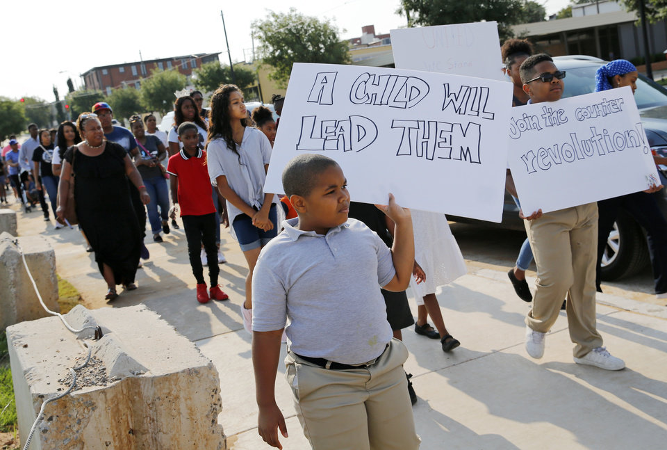 Photo - Collin Walters, 10, holds a sign as he marches with others along NW 10 from Frontline Church to Kaiser's Grateful Bean Cafe to commemorate the 60th anniversary of the Katz Drug Store sit-ins, some of the first civil rights protests in the nation, in Oklahoma City, Saturday, Aug. 18, 2018. The first Katz Drug Store sit-in happened on August 19, 1958. Photo by Nate Billings, The Oklahoman