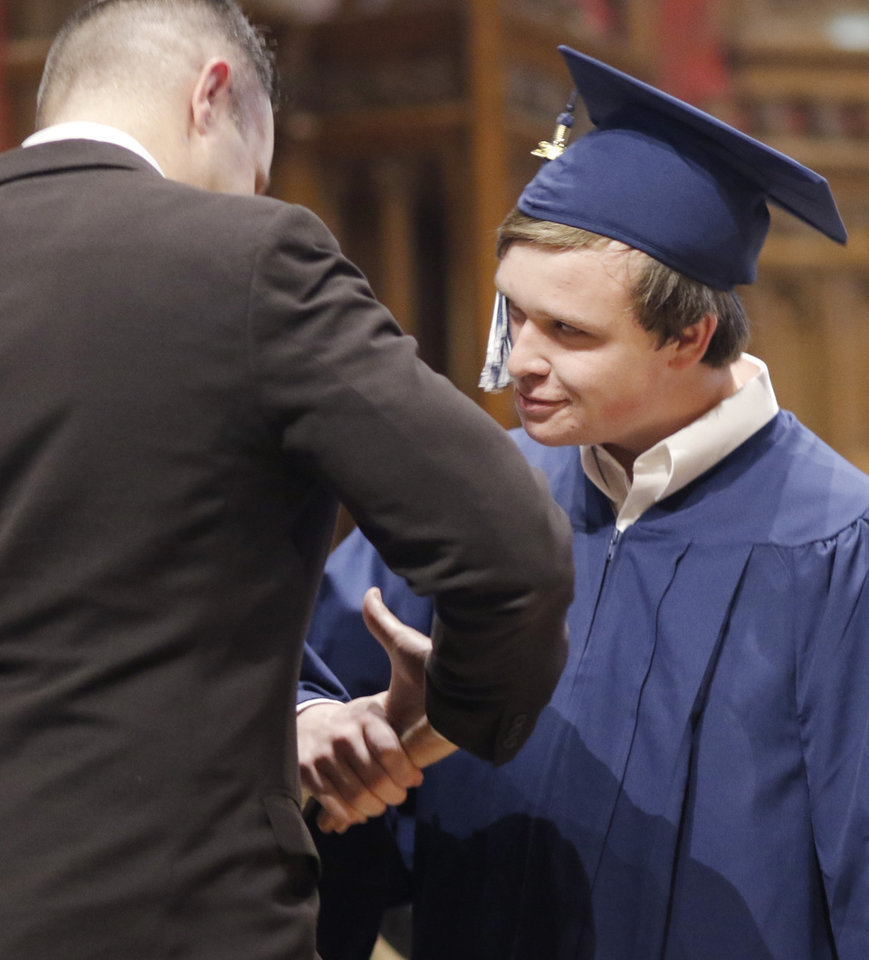 Photo - James is congratulated by Douglas McPherson after being introduced during the Teen Recovery Solutions (TRS) at Mission Academy high school graduation ceremony at St. Paul's Episcopal Cathedral, 127 NW 7th, in Oklahoma City, Thursday, May 26, 2016. Photo by Doug Hoke, The Oklahoman