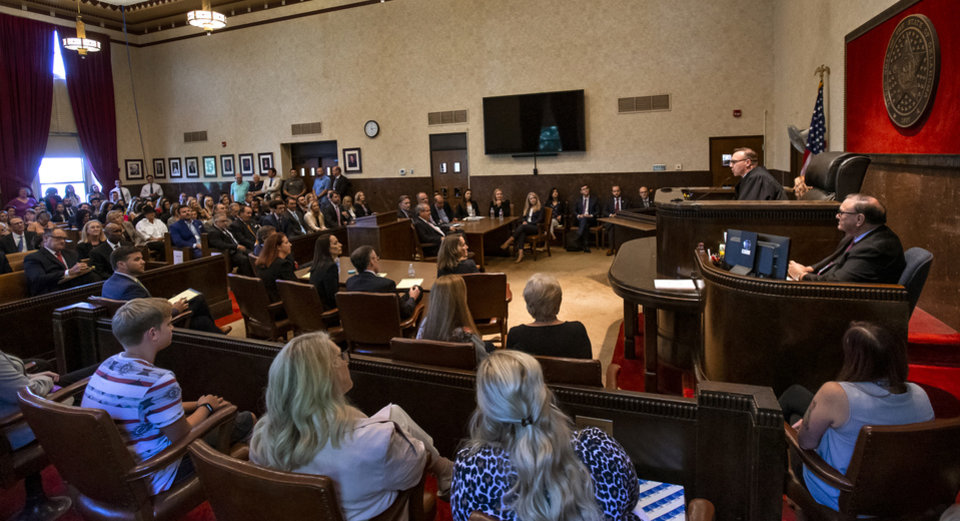 Photo - Judge Thad Balkman reads a summery of his decision to a full courtroom during the opioid trial at the Cleveland County Courthouse in Norman, Okla. on Monday, Aug. 26, 2019. Judge Balkman ruled in favor of the State of Oklahoma, that Johnson and Johnson pay $572 million to a plan to abate the opioid crisis. The proceeding were the first public trial to emerge from roughly 2,000 U.S. lawsuits aimed at holding drug companies accountable for the nationÕs opioid crisis.  [Chris Landsberger/Pool]