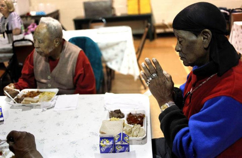 Photo -  Elder Robinson, 85, prays before lunch at the Lincoln Senior Center, 4712 North Martin Luther King Avenue, Friday, Jan. 8, 2009, in Oklahoma City. Photo by Sarah Phipps, The Oklahoman