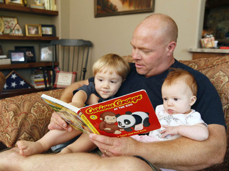 Photo - Andy Brooks reads to 2-year-old son Ben and 4-month-old daughter Abigail at their home in Edmond on Monday. Photo by Paul Hellstern, The Oklahoman  PAUL HELLSTERN