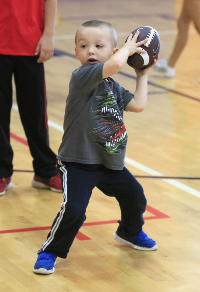 Photo -  Liam Clapper, 3, throws a football during Healthy Kids Day. [PHOTO BY PAUL HELLSTERN, THE OKLAHOMAN]