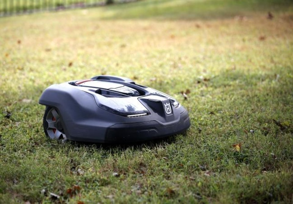 Photo -  A robotic mower moves around a yard Tuesday at a home in Arcadia. [SARAH PHIPPS/THE OKLAHOMAN]