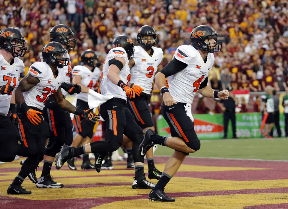 Photo - Oklahoma State's J.W. Walsh (4) runs off the field after scoring a touchdown during the college football game between the Central Michigan Chippewas and the Oklahoma State University Cowboys at the Kelly-Shorts Stadium in Mount Pleasant, Mich., Thursday, Sept. 3, 2015. Photo by Sarah Phipps, The Oklahoman