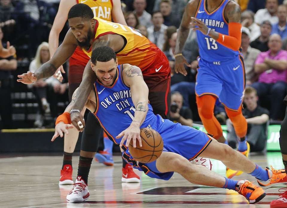 Photo - Utah Jazz forward Royce O'Neale, rear, battles for the ball against Oklahoma City Thunder forward Abdel Nader (11) in the first half during an NBA basketball game Monday, March 11, 2019, in Kearns, Utah. (AP Photo/Rick Bowmer)