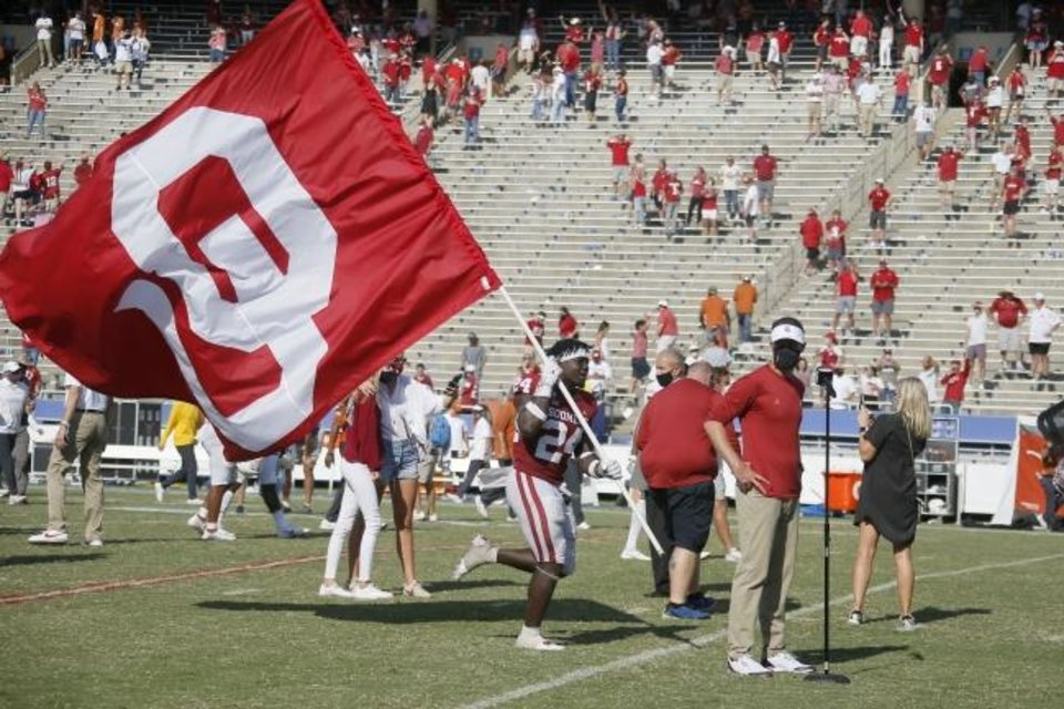 Photo -  Oklahoma's Brian Asamoah (24) carries an OU flag by Oklahoma coach Lincoln Riley after the Red River Showdown college football game between the University of Oklahoma Sooners (OU) and the Texas Longhorns (UT) at Cotton Bowl Stadium in Dallas, Saturday, Oct. 10, 2020. Oklahoma won 53-45 in four overtimes. [Bryan Terry/The Oklahoman]