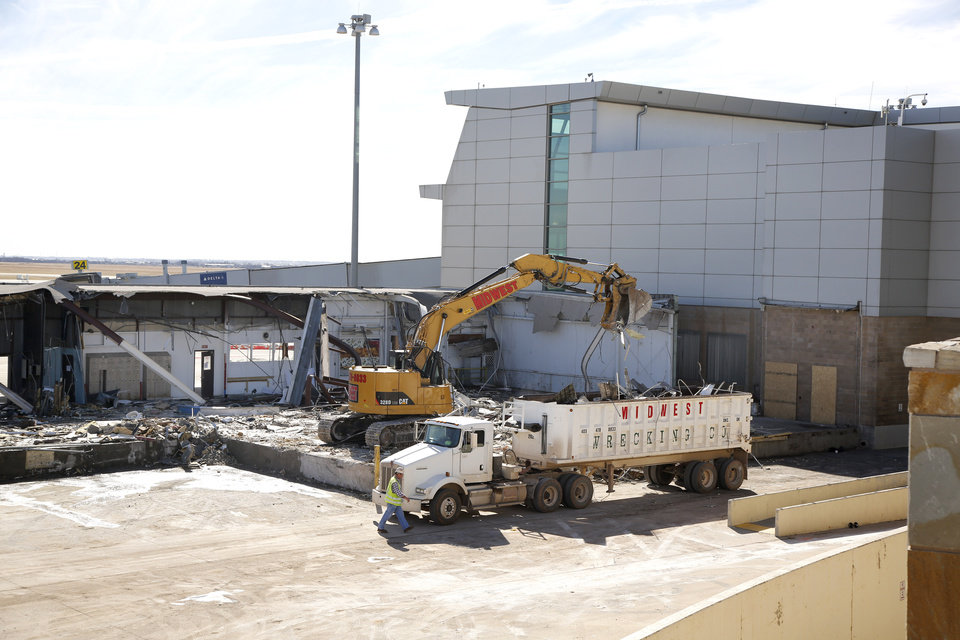 Photo -  Workers demolish a section of a cargo building at Will Rogers World Airport to make room for an expansion project. [Photo By Steve Gooch, The Oklahoman]