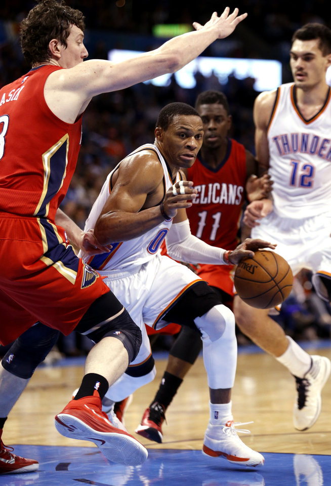 Photo - Thunder's Russell Westbrook (0) tries to go around Pelican's Omer Asik (3) during the second half of an NBA basketball game between the Oklahoma City Thunder and the New Orleans Pelicans at Chesapeake Energy Arena on Dec. 21, 2014 in Oklahoma City, Okla. Photo by Steve Sisney, The Oklahoman