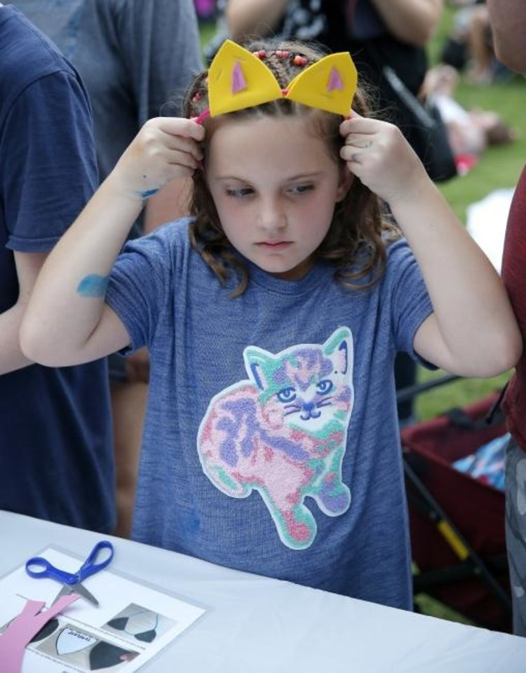 Photo -  Valkyrie Pate, 7, of Edmond, tries on cat ears during last year's Cat Video Festival at the Myriad Botanical Gardens in Oklahoma City. [Sarah Phipps/The Oklahoman Archives]