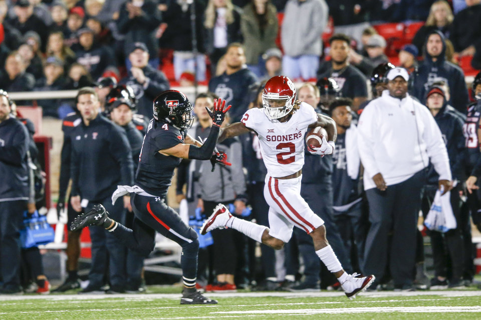 Photo - Oklahoma Sooners wide receiver CeeDee Lamb (2) stiff arms Texas Tech Red Raiders defensive back Desmon Smith (4) during the NCAA football game between the Texas Tech Red Raiders and the Oklahoma Sooners at Jones AT&T Stadium in Lubbock, Texas on Saturday, November 03, 2018. IAN MAULE/Tulsa World
