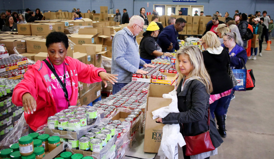 Photo - Volunteer from American Airlines,Patricia Driver, left, hands out food during a free food distribution for federal employees by the Regional Food Bank of Oklahoma at State Fair Park Monday, January 21, 2019.  Photo by Doug Hoke, The Oklahoman
